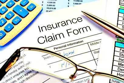 Close up of handwritten Insurance Claim Form with pen and calculator