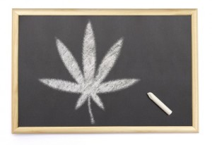 Blackboard with a chalk and the shape of the cannabis symbol dra