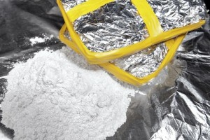 Two bricks of cocaine wrapped in foil beside a heap of cocaine.